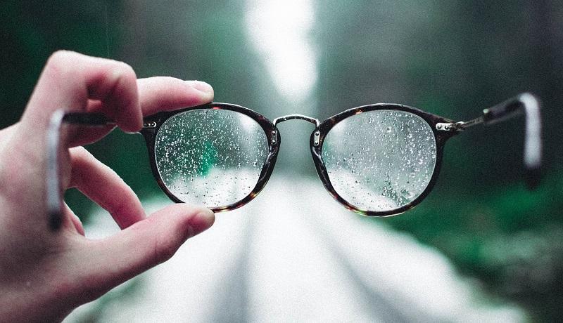 Bril met waterdruppels erop wordt voor een bosweg gehouden